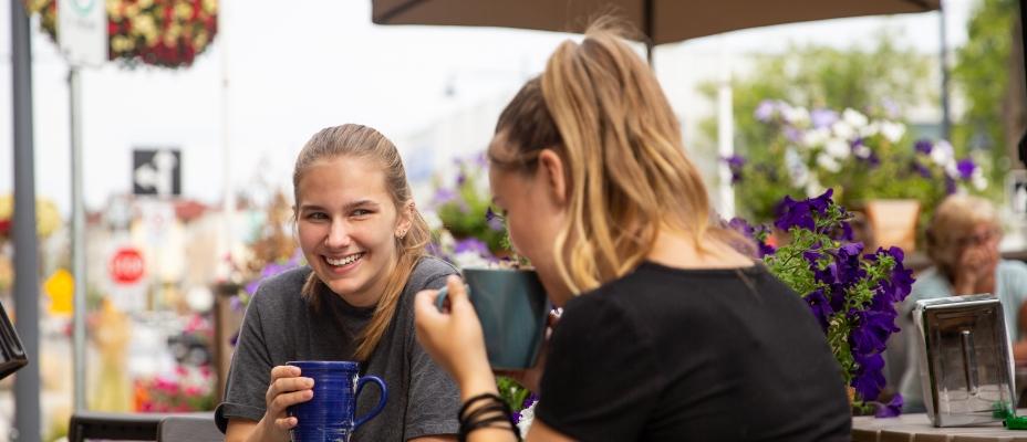 Patrons visiting at an outdoor cafe patio.